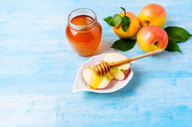 Rodajas de manzana con miel sobre madera azul