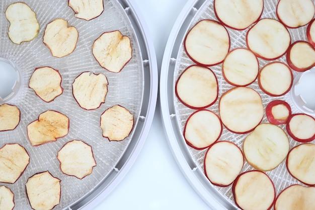 Rodajas de manzana seca y fresca en bandejas de secador de frutas eléctrico especial