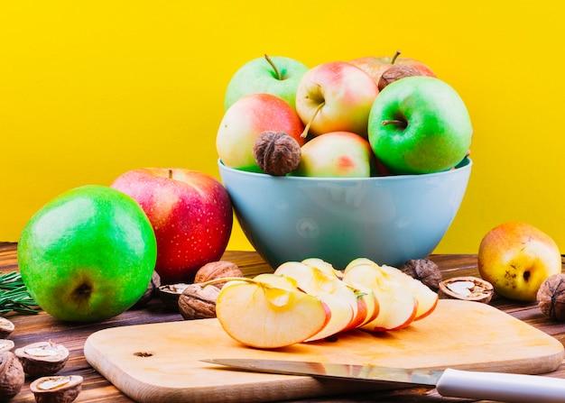 Rodajas de manzana sobre tabla de cortar con frutas y nueces
