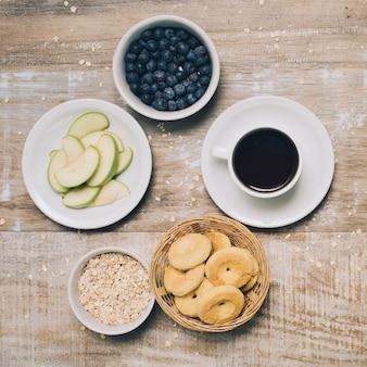 Rodajas de manzana; tazón de avena; galletas; tazón de arándanos y taza de café en madera con textura