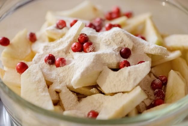 Rodajas de manzanas y arándanos espolvoreados con harina en un bol de vidrio.