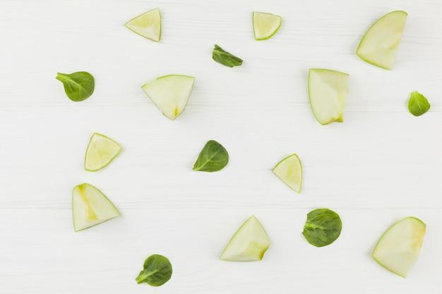 Rodajas de manzanas, limón y hojas verdes sobre un fondo blanco