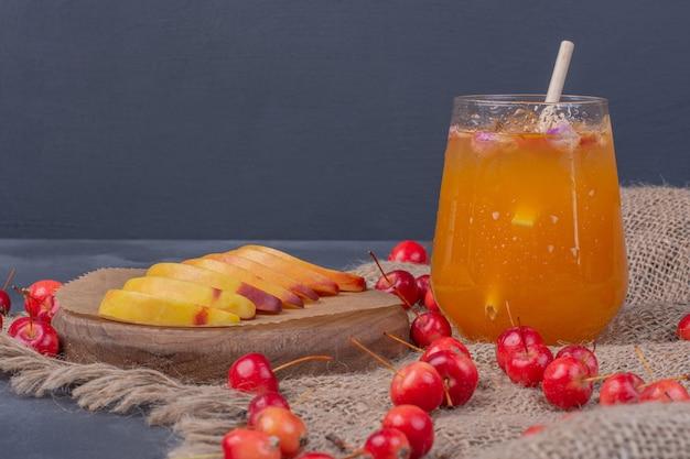 Rodajas de melocotón, cerezas y vaso de jugo de fruta en azul.