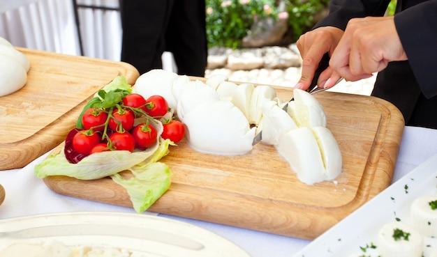 Rodajas de mozzarella del camarero durante la recepción de una boda