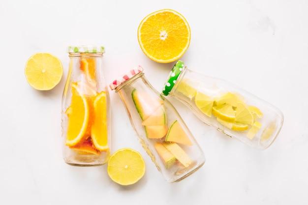 Rodajas de naranja y botellas de vidrio con cítricos cortados.