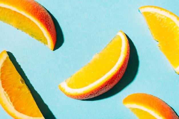 Rodajas de naranja madura con piel brillante sobre superficie turquesa.