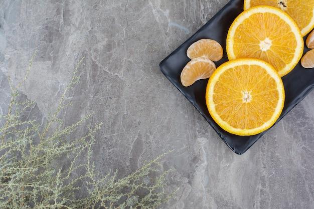 Rodajas de naranja y mandarina en placa negra.