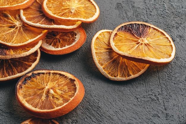 Rodajas de naranja seca sobre fondo gris oscuro