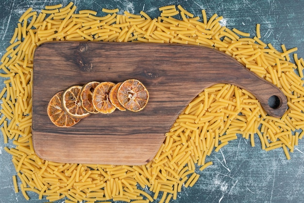 Rodajas de naranja sobre tabla de madera con un montón de pasta cruda. foto de alta calidad