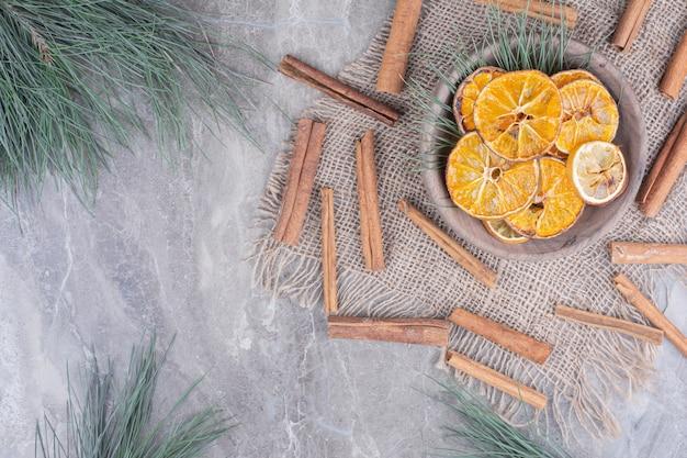 Rodajas de naranja en una taza de madera con ramas de canela alrededor