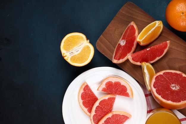 Rodajas de naranja y uva en el fondo azul.
