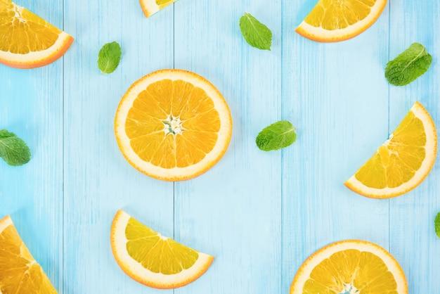 Rodajas de naranjas frescas con hojas de pepperment sobre fondo de madera azul claro