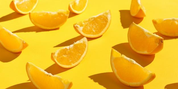 Rodajas de naranjas sobre un fondo amarillo, papel tapiz de patrón brillante.