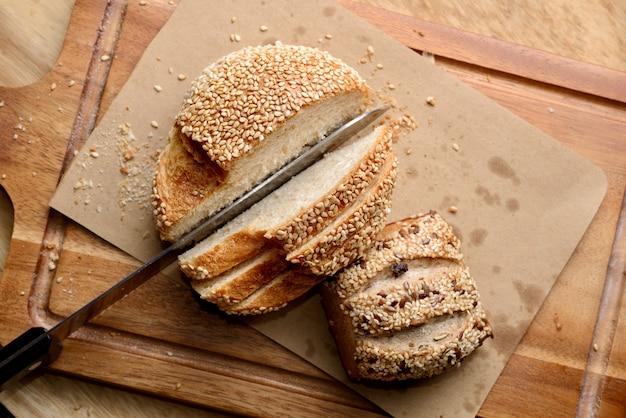 Rodajas de pan de sésamo casero en plato de madera.