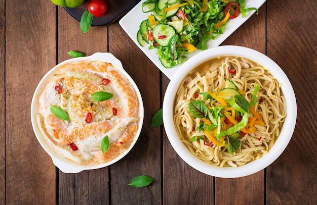 Rodajas de pescado rojo y blanco al horno con miel y jugo de lima, servido con ensalada fresca y fideos suaves en caldo de miso