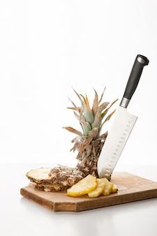 Rodajas de piña en rodajas con un cuchillo sobre una tabla de cocina