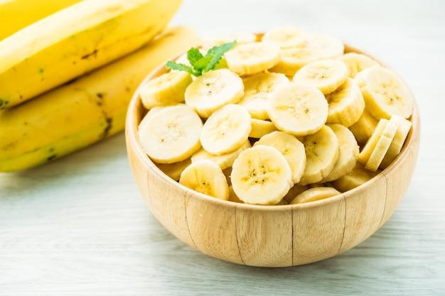 Rodajas de plátano amarillo crudo en un tazón de madera