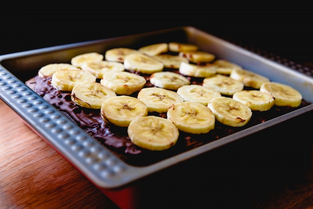 Rodajas de plátano en un pastel en una bandeja antes de hornearlo.