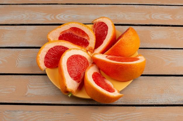 Rodajas de pomelo fresco jugoso suave forrado dentro de un plato amarillo sobre una rústica ligera