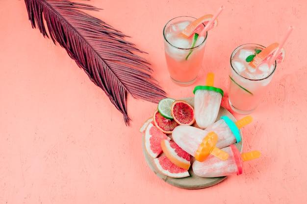Rodajas de pomelo; jugos y paletas con hojas sobre fondo con textura coral