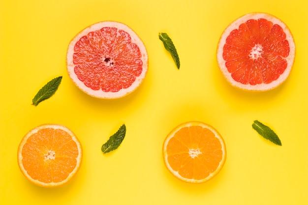 Rodajas de pomelo jugoso naranja y hojas verdes en superficie amarilla