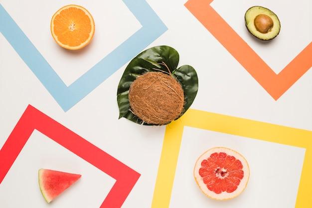 Rodajas de pomelo naranja sandía aguacate y coco en la hoja de monstera