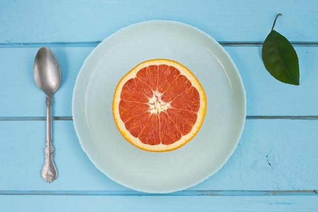 Rodajas de pomelo rojo fresco en un plato con fondo de madera azul rústico.