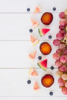 Rodajas de pomelo; sandía; arándanos; ciruela y uvas en mesa de madera blanca.