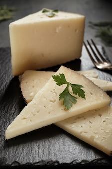 Rodajas de queso curado y tenedor