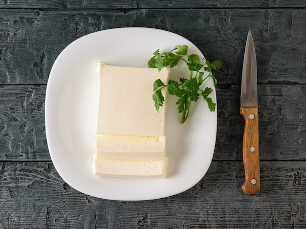 Rodajas de queso serbio con un cuchillo y perejil en la mesa del pueblo.