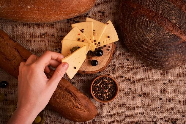 Rodajas de queso sobre mesa de madera entre diferentes tipos de pan.