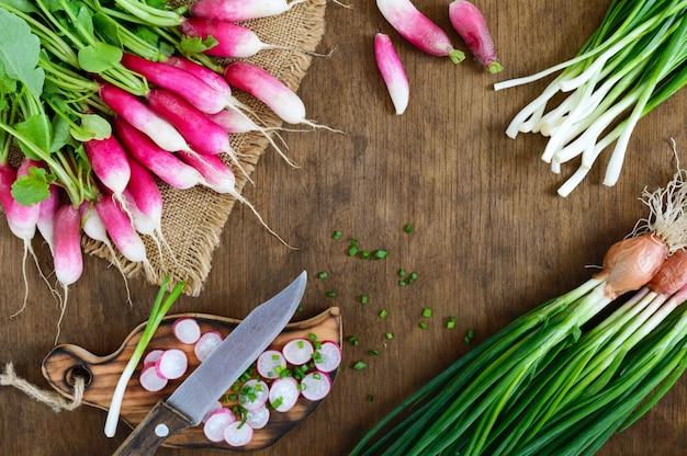 Rodajas de rábanos rojos frescos y cebollas jóvenes verdes sobre fondo blanco de madera. dieta saludable con rábano. ingredientes para una ensalada ligera de verduras de primavera. la vista superior