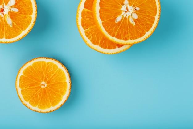 Rodajas y rodajas de pulpa de naranja sobre un azul brillante