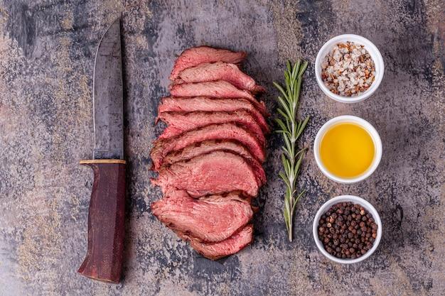 Rodajas de rosbif con romero, sal, pimienta y aceite de oliva.