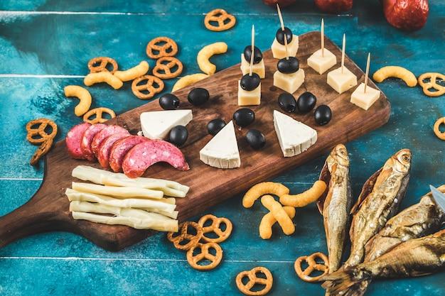 Rodajas de salchicha con cubitos de queso, aceitunas y galletas en una tabla de madera con pescado seco en la mesa azul