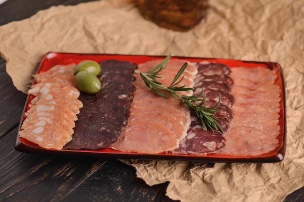 Rodajas de salchichas en un plato rojo. con romero y aceitunas. en una mesa de madera