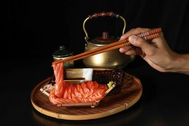 Rodajas de salmón pescado sashimi en el bote con los palillos en la mano.