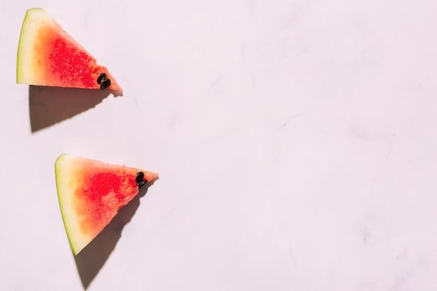 Rodajas de sandía madura sobre superficie rosa