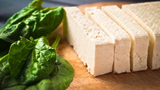 Rodajas de tofu crudo y espinacas
