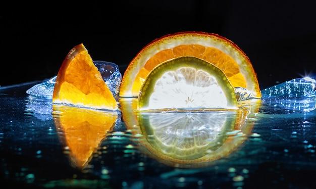 Rodajas transparentes de naranjas y limones sobre el vaso.