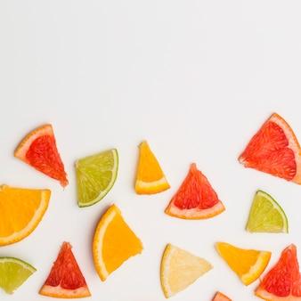Rodajas triangulares de naranjas; pomelo y limón sobre fondo blanco