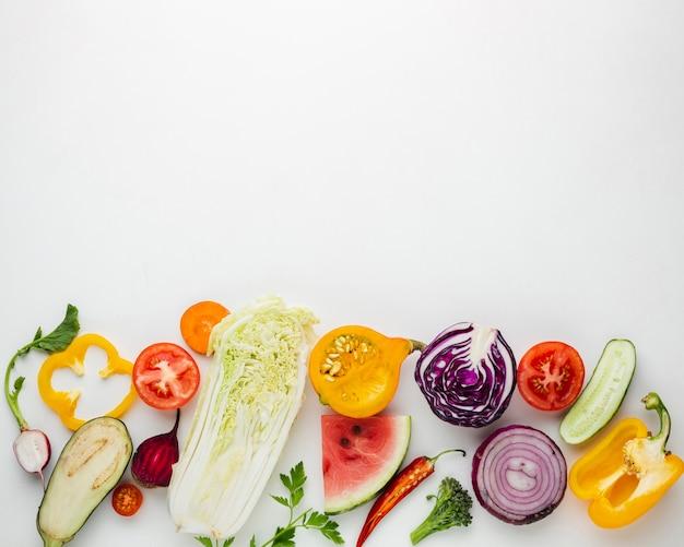 Rodajas de verduras sobre fondo blanco con espacio de copia
