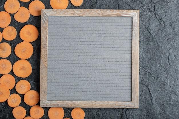 Rodajas de zanahoria fresca sobre fondo negro alrededor del marco. foto de alta calidad
