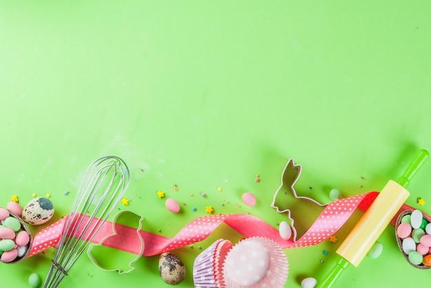 Rodillo, batidor para batir, cortadores de galletas, azúcar espolvoreado y harina sobre fondo verde claro