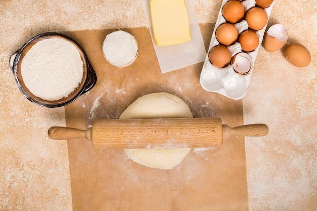 Rodillo en bola de masa con ingredientes en mostrador de madera