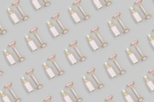 Rodillo facial de cuarzo rosa de cristal y colágeno antienvejecimiento, suero en frasco de vidrio sobre gris