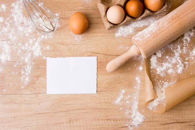 Rodillo con huevos en estante, papel y harina.