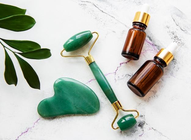 Rodillo de jade de masaje facial con producto cosmético sobre fondo de mármol blanco
