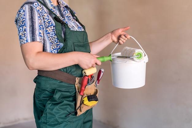 Rodillo para pintar y balde en manos femeninas