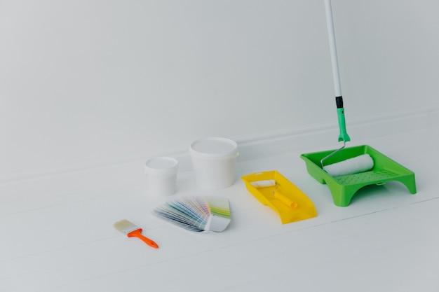 Rodillo de pintura en bandeja, pincel y muestra de color aislado sobre blanco